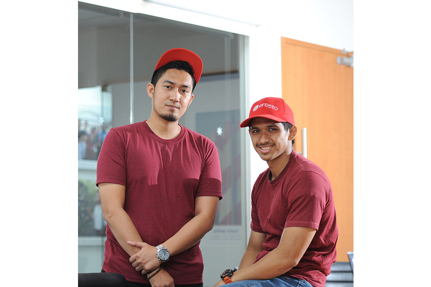 Two smiling men wearing red cap and t-shirt