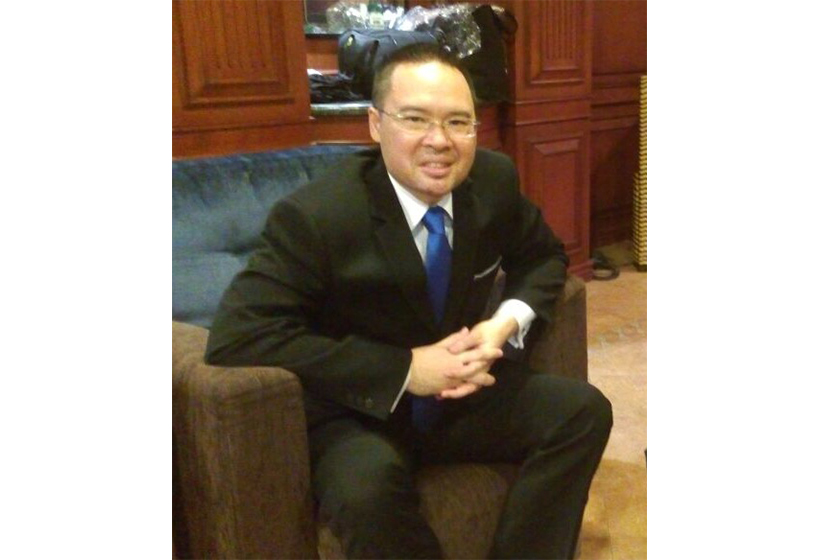 A man with glasses wearing formal suit is sitting on the sofa