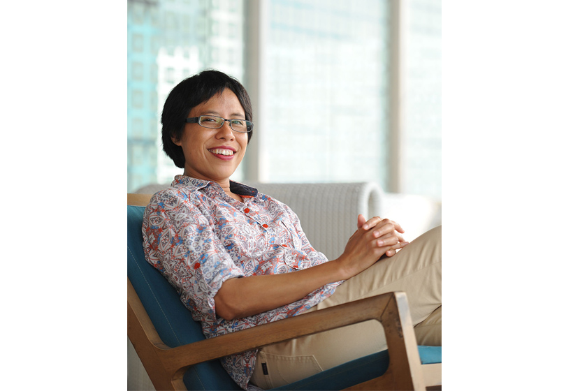 A smiling woman wearing patterned shirt sitting on the sofa