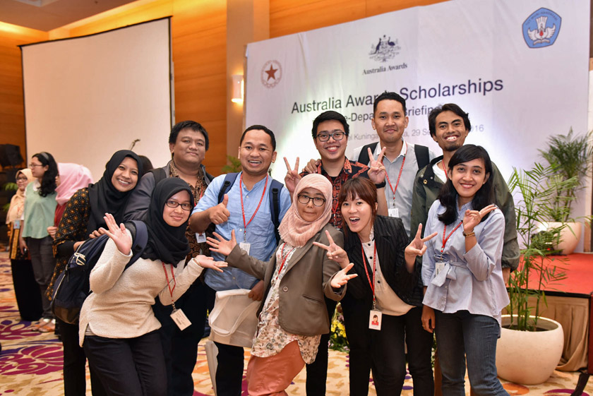 A group of students posing in front of Australia Awards Scholarships banner