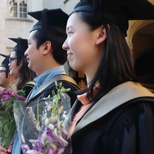 A group of graduating students holding bouquets of flowers