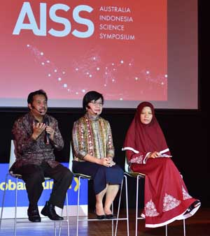 Three people are sitting on a chair on the stage with AISS logo appearing on the screen behind them