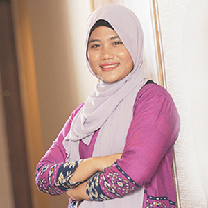 A woman with hijab wearing pink dress is smiling