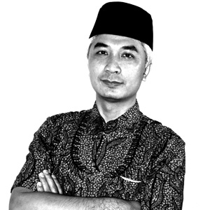 A man wearing peci hat and batik shirt in black and white photo