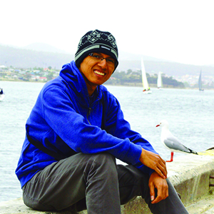 A man wearing black cap and blue jacket is sitting by the bay
