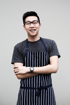 A young man with glasses wearing striped apron is smiling