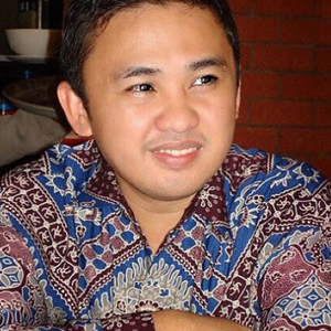 A man wearing batik shirt crossing arms